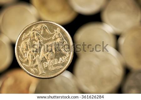 Australian one dollar coin over blurred golden background. - stock photo