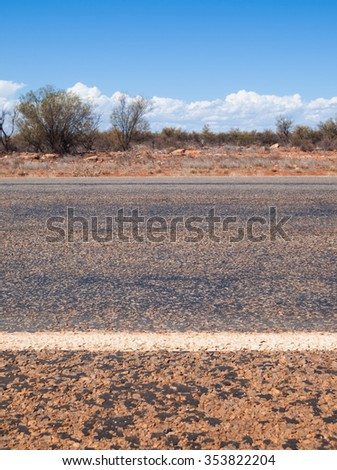 Australian outback road markings and blue sky - stock photo