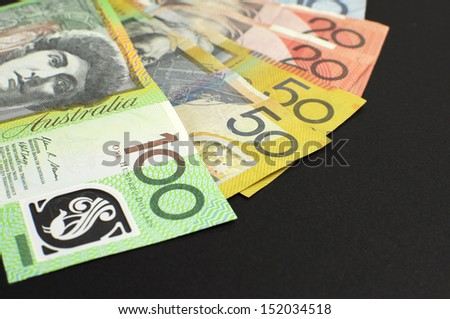 Australian paper money, including one hundred, twenty, ten, five and fifty dollar notes against a black background, with copy space. - stock photo