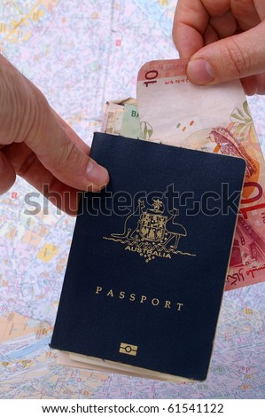 australian passport and holder on top of paris map with cash exchanging hands - stock photo