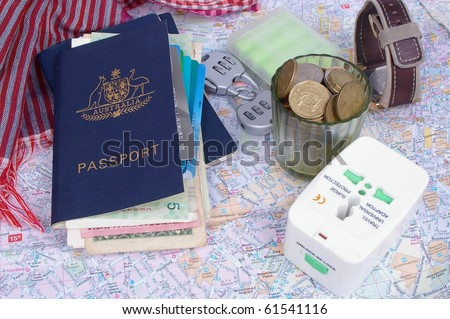 australian passport and holder with travel items on top of paris map