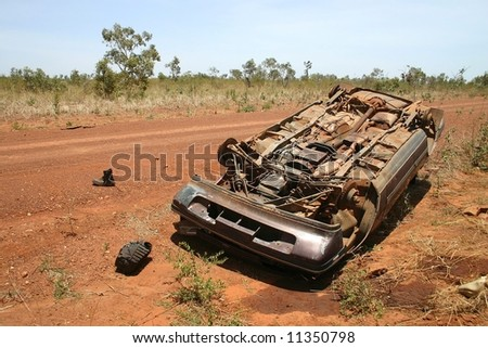 Australian red rural road with an overturned obsolete rusted car on the roadside. Pollution Damage. Tanami road, Western Australia - stock photo