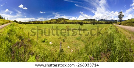 australian remote rural land near Barrington tops one hot summer day with green cultivated grass in developed agricultural property panoramically shot from road - stock photo