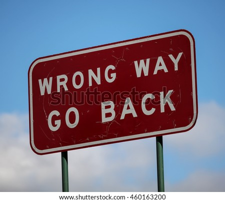 Australian road sign, Wrong Way Go Back, often found where on and off ramps to highways could be confused and people might drive on the wrong road or where the road is a single direction - stock photo