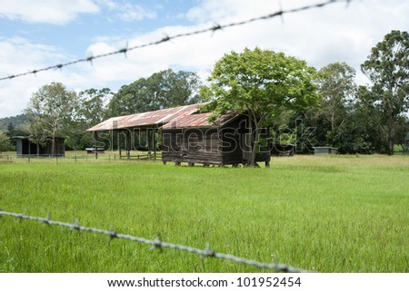 Australian rural landscape, old farm shed in field beyond the barbed wire fence. - stock photo