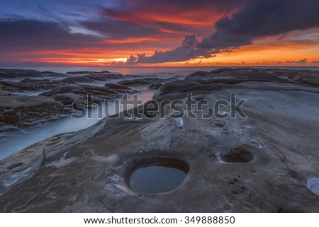 Australian seascape at dawn with rocks in foreground - stock photo