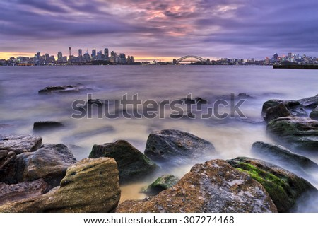 Australian Sydney cityline from CBD via Harbour Bridge to North Sydney in a distance over Harbour waters at low tide with foreground stones uncovered and wet at sunset - stock photo