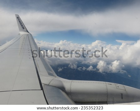 AUSTRIA - CIRCA SEPTEMBER 2014: Ryanair aircraft flying high in the sky over Austria (view from side window towards the sky)