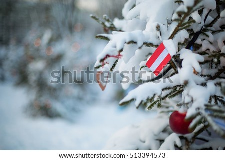Austria flag Christmas holiday greeting card. Christmas tree covered with snow and a Austrian flag. Winter scene background outdoor