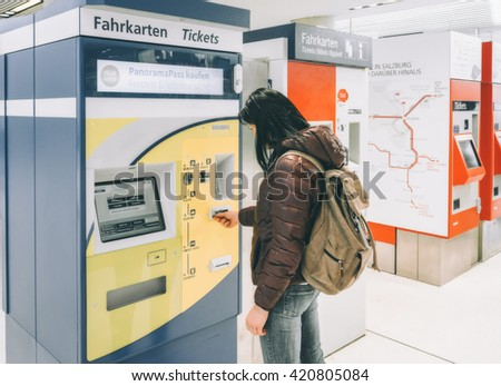 AUSTRIA, SALZBURG - APRIL 21, 2016: She buys a train ticket at the ticket machine at the train station. Traveling by train at the Alpine Railroad.