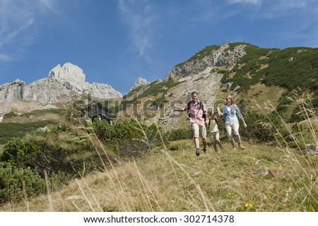Austria,Salzburg Country,Filzmoos,Family hiking on alpine pasture - stock photo