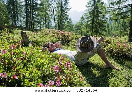 Austria,Salzburg Country,Man relaxing on alpine pasture on mountains of Niedere Tauern