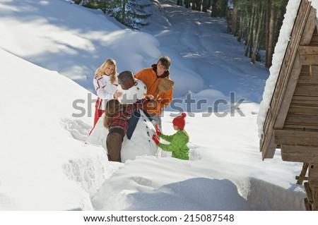 Austria, Salzburger Land, Altenmarkt, Family building snowman, elevated view - stock photo