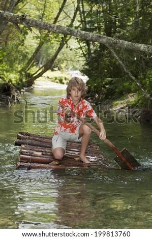 Austria, Salzburger Land, Boy on timber raft, paddling - stock photo