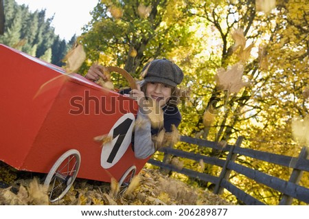 Austria, Salzburger Land, Boy sitting in soapbox car, smiling