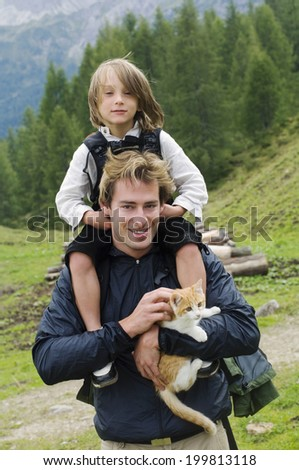Austria, Salzburger Land, father with son on shoulders - stock photo