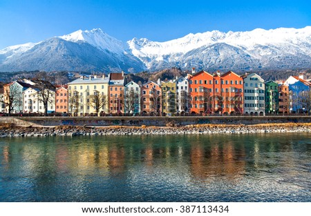Austria, Tirol, Innsbruck, the Mariahilf strasse colored houses on the Inn river with the snowy mountains in the background