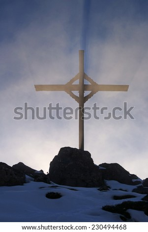 Austria, tyrolean alps, wooden cross with backlight and a dramatic sky - stock photo