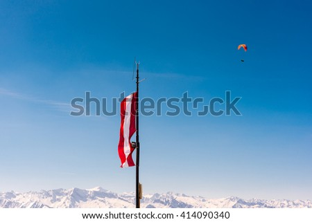 austrian flag fying from an antenna in the alps on a winter day with a paraglider in the back - stock photo