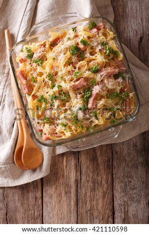 Austrian noodles with ham and parmesan close-up in a glass baking dish on the table. Vertical view from above  - stock photo