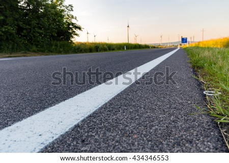Austrian road close to wheat fields and wind turbines, Kittsee