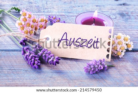 Auszeit- Relaxation - rustic floral background with dainty lavender spikes and flowers with a burning aromatherapy candle surrounding a label with the word - Auszeit - on pale blue wooden boards