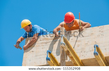 Authentic construction builders working together for nailing wooden cement formwork in place - stock photo