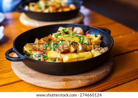 Authentic fried potatoes with bacon and parsley on black pan. Morning atmospheric lighting, fashionable trendy spot soft focus. Preparation for design creative menu. - stock photo