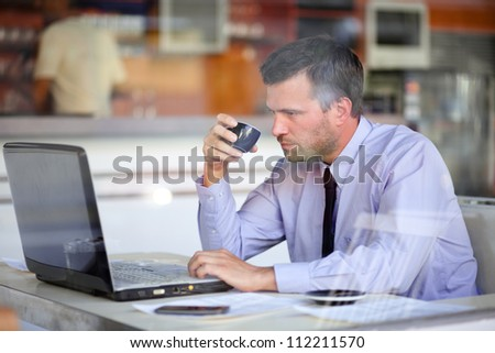 Authentic image of a businessman drinking coffee while working in a cafe - stock photo
