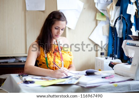 Authentic image of a fashion designer working in her studio - stock photo