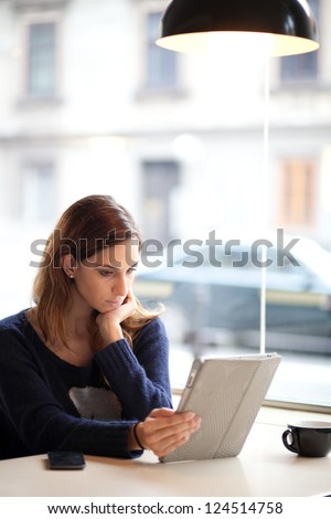 Authentic image of a young woman using tablet computer in a cafe
