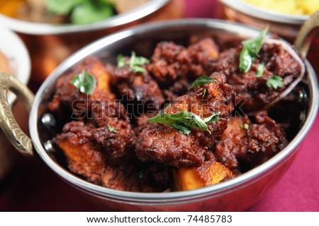 Authentic Kerala chicken fry garnished with curry leaves, a popular South Indian dish of chicken fried in a spicy coating. - stock photo