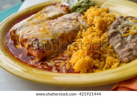 Authentic Mexican chimichanga burrito with sour cream jalapeno and cilantro - stock photo