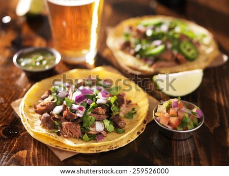 authentic mexican tacos with beer on wooden table shot with selective focus - stock photo