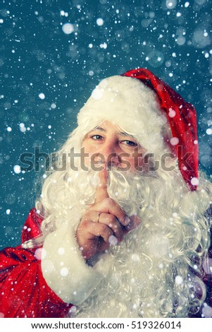 Authentic Santa Claus. Santa Claus presses a finger to his lips. Christmas tale.
