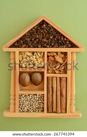 Authentic Sri Lankan spices in decorative wooden house shaped box on green background in vertical format - stock photo