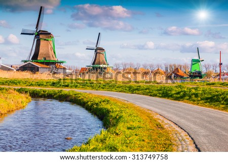 Authentic Zaandam mills on the water channel in Zaanstad village. Zaanse Schans Windmills and famous Netherlands canals, Europe - stock photo