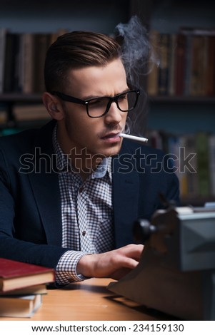 Author at work. Confident young author working at the typewriter and smoking cigarette while sitting at his working place with bookshelf in the background  - stock photo