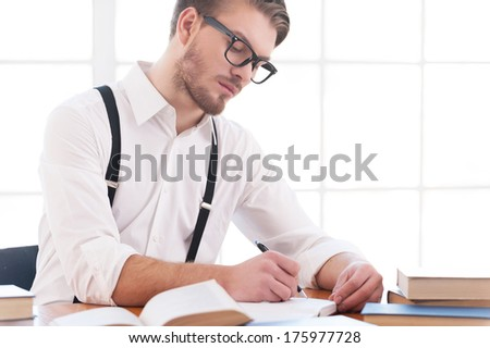 Author at work. Confident young man in shirt and suspenders writing something in note pad while sitting at his working place - stock photo