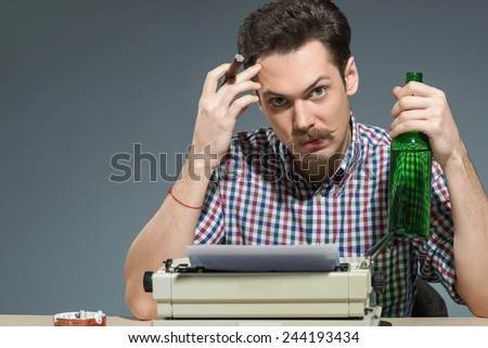 Author at work. Creative young author working at the typewriter, smoking cigar and drinking alcohol while sitting at his working place against grey background - stock photo
