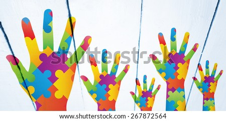 Autism awareness hand against painted white wooden planks