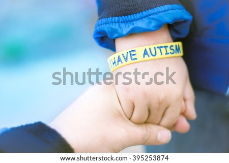 Autism Awareness Picture-I have Autism -Autism Mom holding hand her Autistic Child  - stock photo