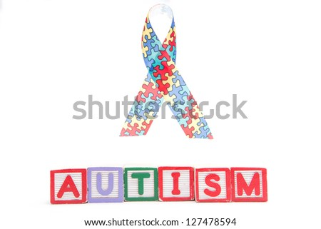 Autism awareness ribbon above letter blocks spelling autism on white background - stock photo