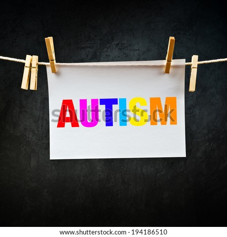 Autism printed on paper hanging on rope. Concept image for disorder of neural development. - stock photo