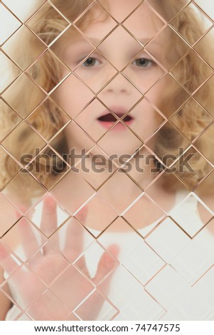 Autistic Child Blurred Behind Pane Of Glass - stock photo