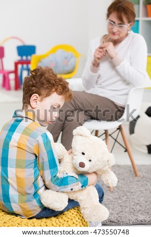 Autistic child holding a teddy bear with his therapist at the background