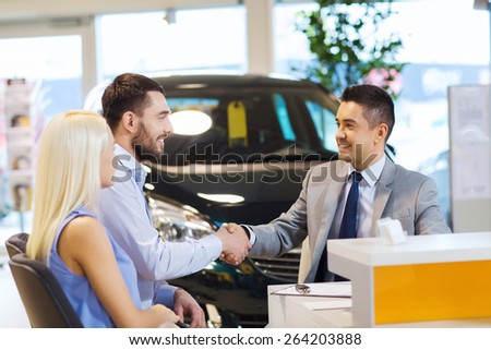 auto business, car sale, and people concept - happy couple with dealer shaking hands in auto show or salon - stock photo