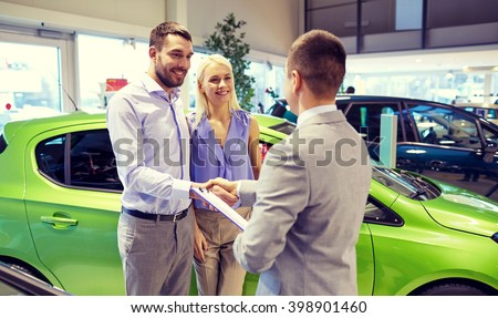 auto business, car sale and people concept - happy couple with dealer shaking hands in auto show or salon - stock photo