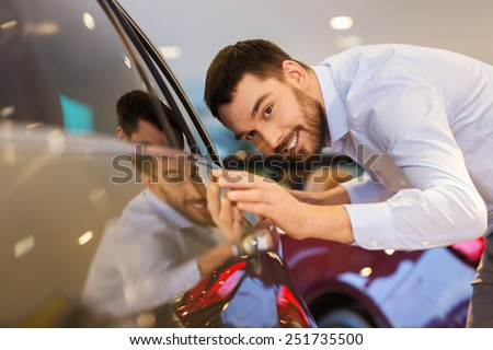 auto business, car sale, consumerism and people concept - happy man touching car in auto show or salon - stock photo