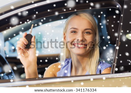 auto business, car sale, consumerism and people concept - happy woman taking car key from dealer in auto show or salon over snow effect - stock photo